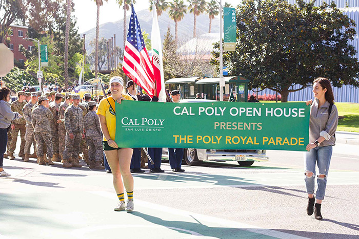 Photo of two female students holding a banner for the Poly Royal Parade at a past Open House on campus.