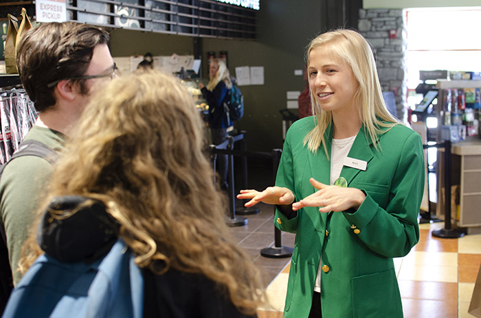 A female student, wearing a green blazer, talks to two other people as part of Campus Dining's new health ambassador program.