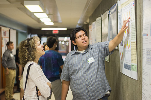 A student discusses his research during a past research conference with the College of Science and Mathematics.