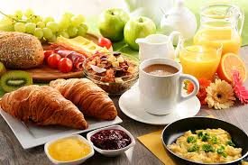Photo of breakfast foods, including coffee, croissants, orange guide and fruit.