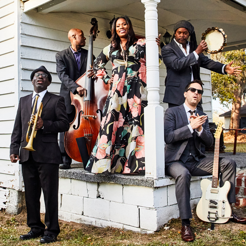 Photo of the South Carolina-based quintet Ranky Tanky, standing outdoors on a front porch with their instruments.