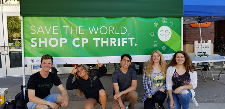 Students pose under a sign reading Save the World, Shop CP Thrift.
