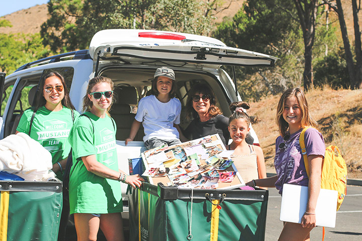 New and current Cal Poly students pose with family for a photo during Mustang Move-In.