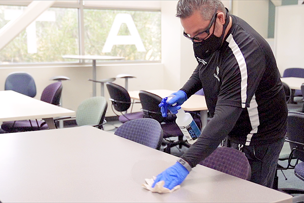 Photo of an employee with a face covering and gloves cleaning a desk inside a classroom.
