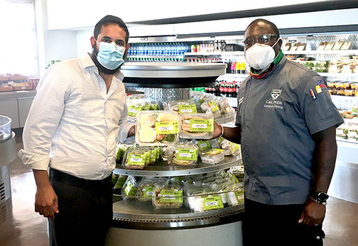Rabbi Chaim Hilel, left, with Campus Dining Executive Chef Resford Abrigo, pose in front of some kosher offerings.