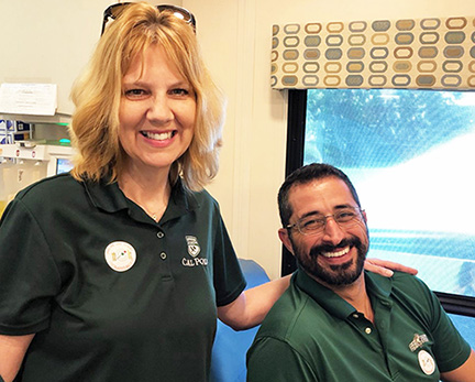 Two Cal Poly employees pose inside the blood drive mobile center.