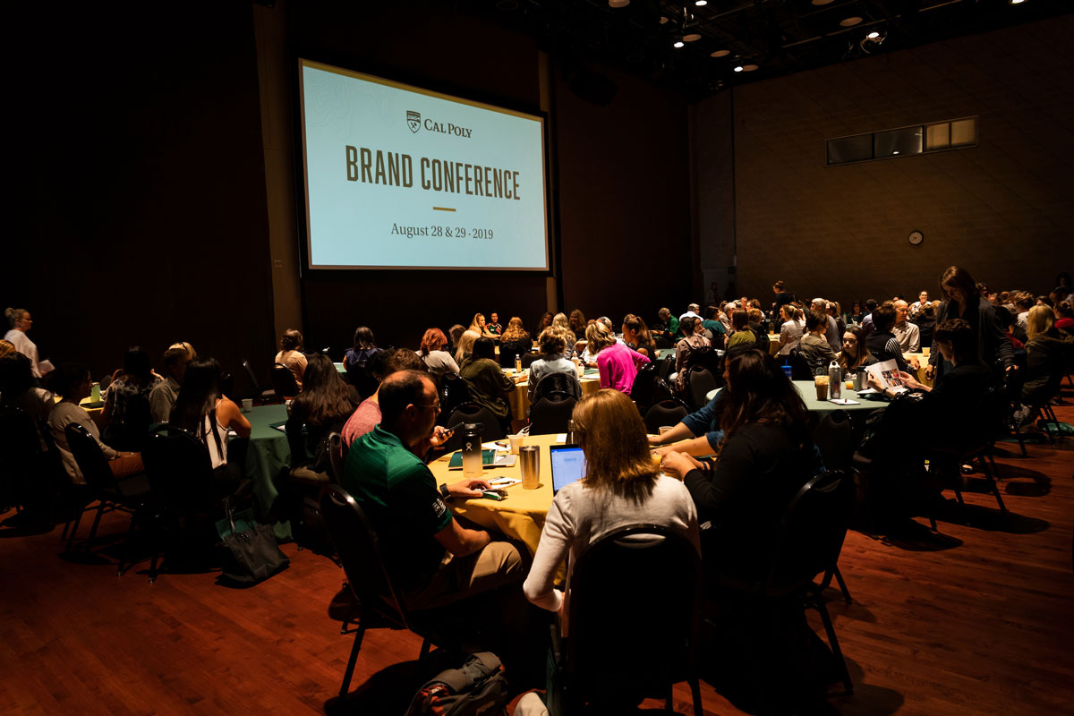 Photo of attendees of Cal Poly's Brand Conference sitting at tables during an event in the PAC Pavilion.