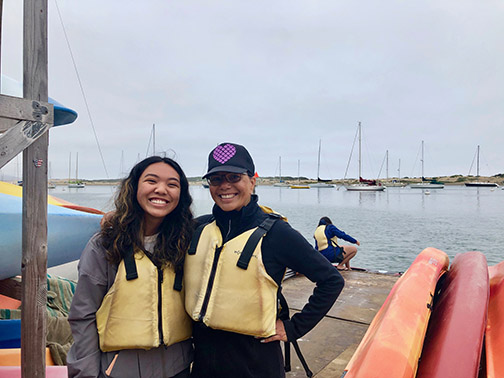 A Cal Poly employee poses with a student by kayaks in Morro Bay.