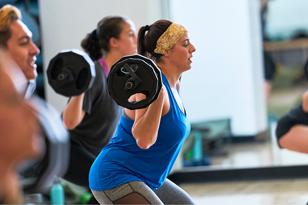 Photo of a woman and other class members lifting weights during a class at the Cal Poly Recreation Center