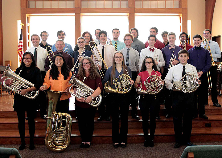 Members of all that brass pose with their instruments.