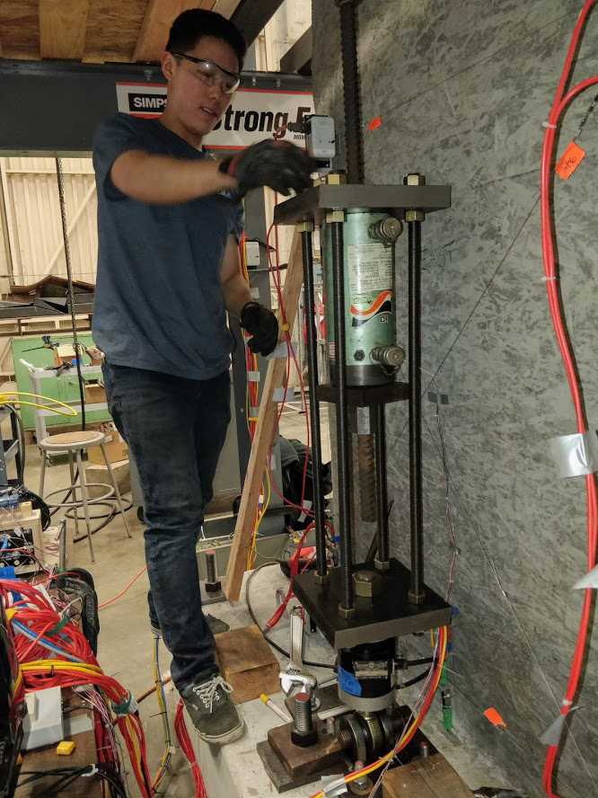 Graduate student researcher Jerry Luong makes final adjustments to the axial load system before testing a concrete wall in 2019. The NSF-funded actuator system will enable higher and more consistent application of axial and lateral forces using computerized control of multiple actuators via a new hydraulic pump. Photo by Rory de Sevilla.