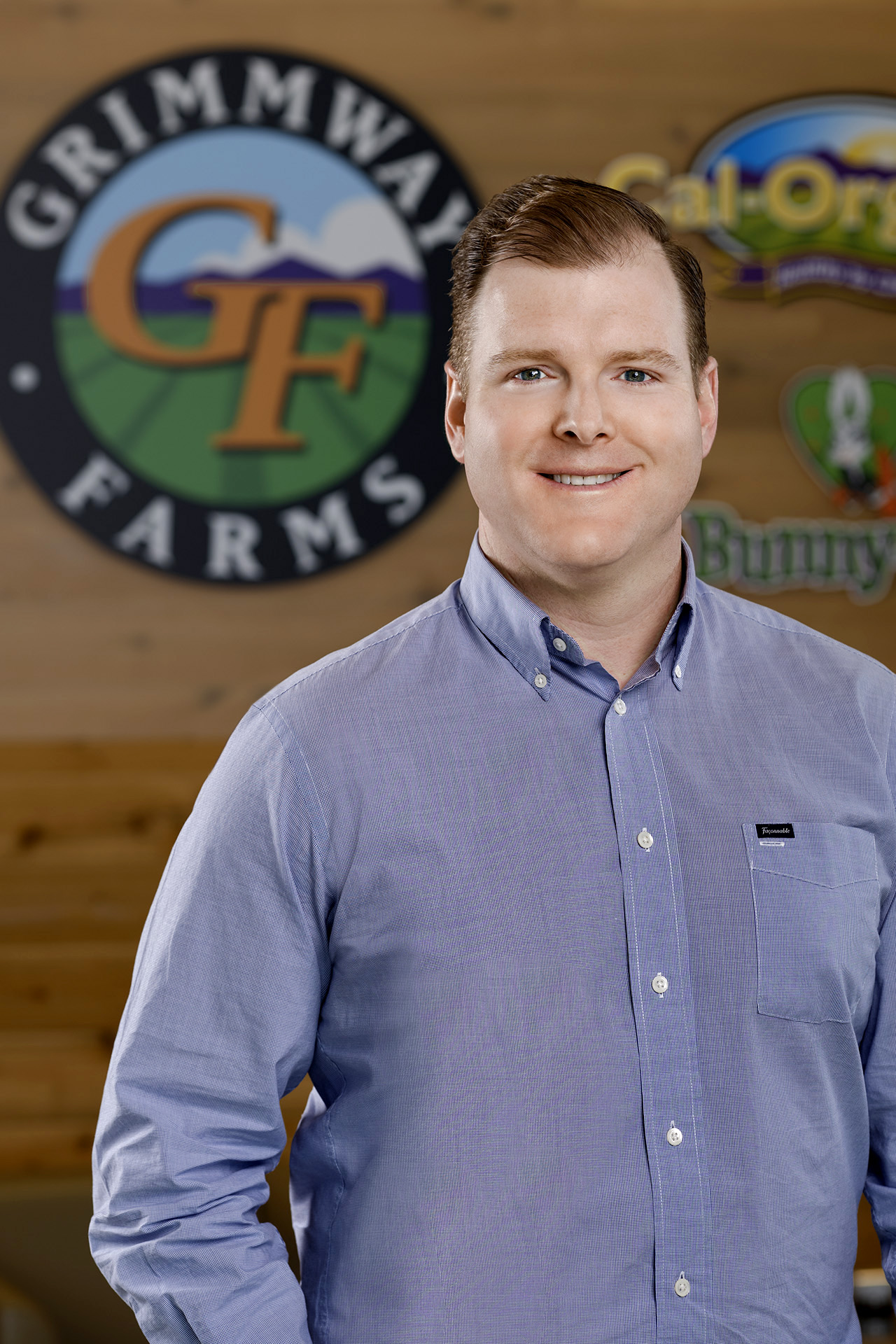 Brandon Grimm stands in front of farm logo