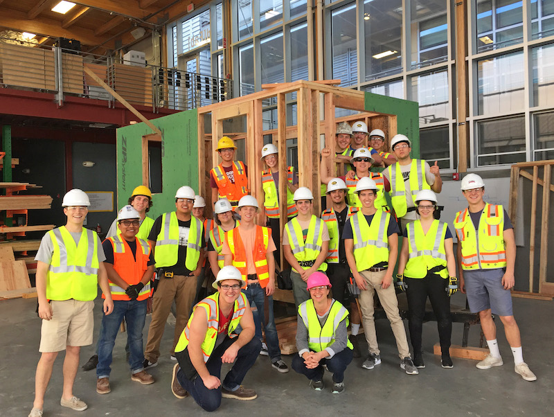 Cal Poly construction management students pose with their structure at the end of the first week of construction.The students had completed the framing and secured the walls to the trailer.