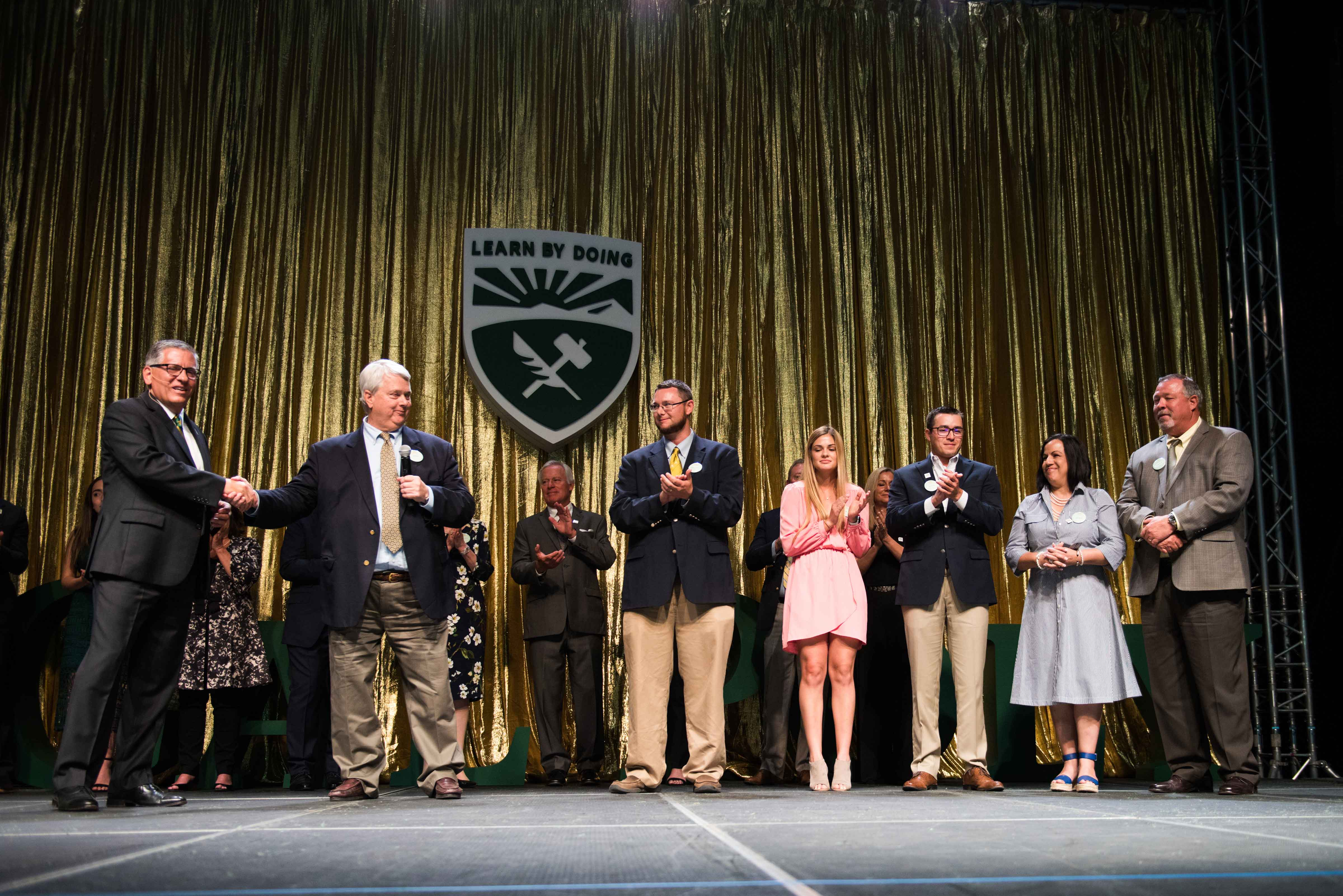 Cal Poly President Jeffrey D. Armstrong, James Boswell, John Ronca, Cameron Boswell, Bridget Dias, Cody Boswell, Catherine Wurzel, and George Wurzel, during the announcement of the Boswells' $10 million gift made in honor of George Wurzel. The George Wurzel Plant Sciences Building will include classrooms and labs and will be adjacent to greenhouses, processing facilities and a farmers' market. The building will unite multiple disciplines to focus and enhance work in plant, earth and soil sciences along with agricultural engineering in one state-of-the-art complex.