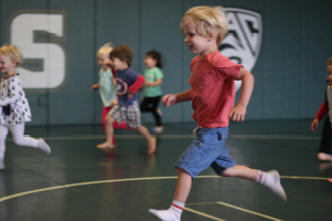 A photo of children running across a gym floor.