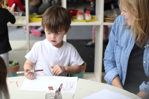 Photo of an adult watching a child color with a marker.