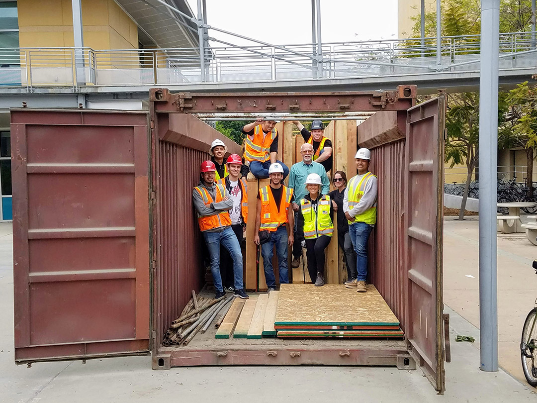 Students and faculty members pose in the container with the exterior wall panels. In the top row, from left to right, are construction management students Jeremiah Eseed, of Brentwood, California; Brent Underwood, of Arroyo Grande, California; and Brendan Mulholland, of Grass Valley, California. In the bottom row, from left to right, are construction management students Luis Badillo, Matthew Sharman, of San Jose, California; Patrick Shami, of San Rafael, California; construction management faculty member Greg Starzyk; construction management student Avery Spector, of Sacramento, California; architecture faculty member Maggie Kirk; and construction management student John Espino.