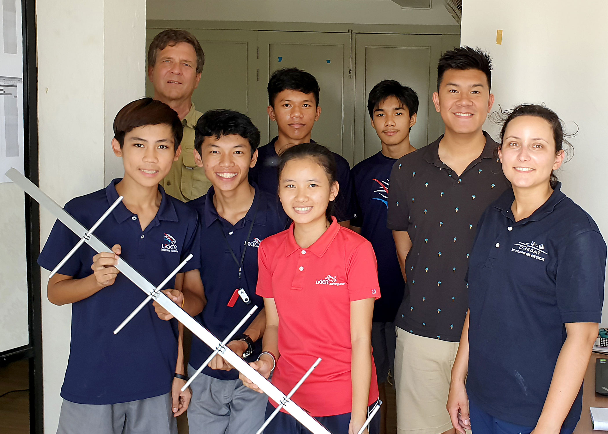 Pauline Faure, an assistant professor of aerospace engineering at Cal Poly, at right, and Justin Nguyen, a Cal Poly computer engineering senior from Fremont, California, second from right, with the group of science, technology, engineering and mathematics seniors from the Liger Leadership Academy who want to build a small satellite hold the handheld antenna for the LigerSat ground station. Also pictured, at rear left, is Doug Bender, a retired Boeing Co. engineer who knew about CubeSats through his former job and connected the Liger Academy with Cal Poly.