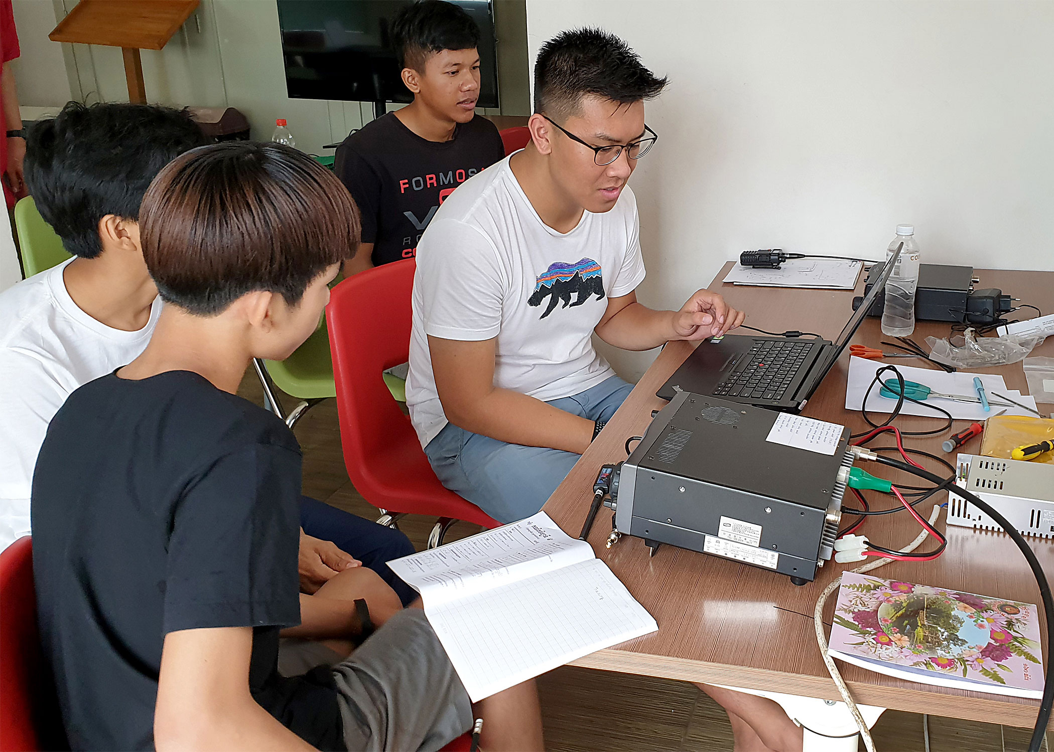 Nguyen instructs several Liger Leadership Academy students in how a tracking ground station works.
