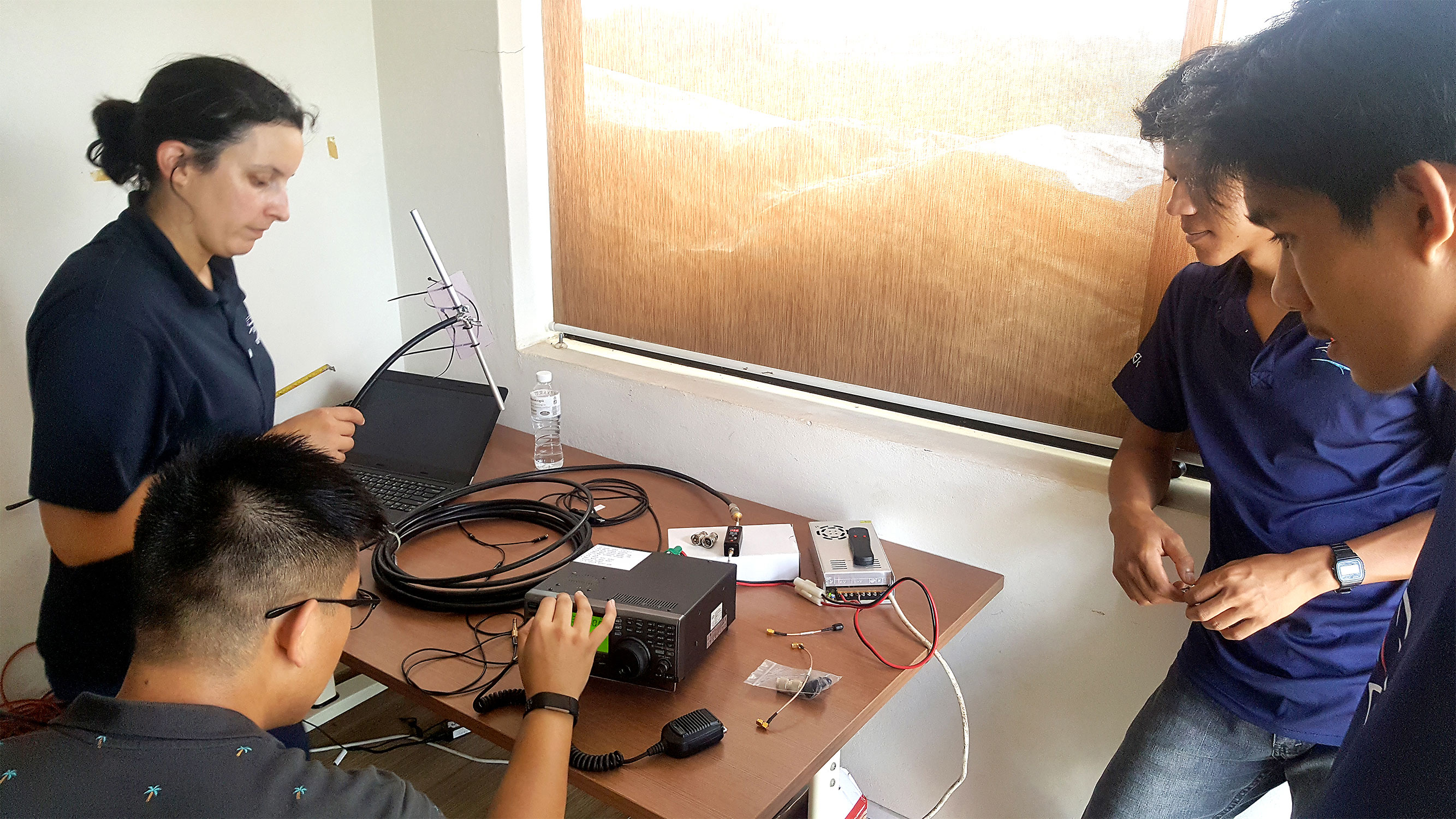 From left, Faure holds an antenna while Nguyen does a test of the ground station satellite tracking equipment as a pair of Liger Leadership Academy students watch. The Cambodian students hope to build their nation's first CubeSat. The ground station is key to tracking its program and necessary for downloading data from orbiting satellites.