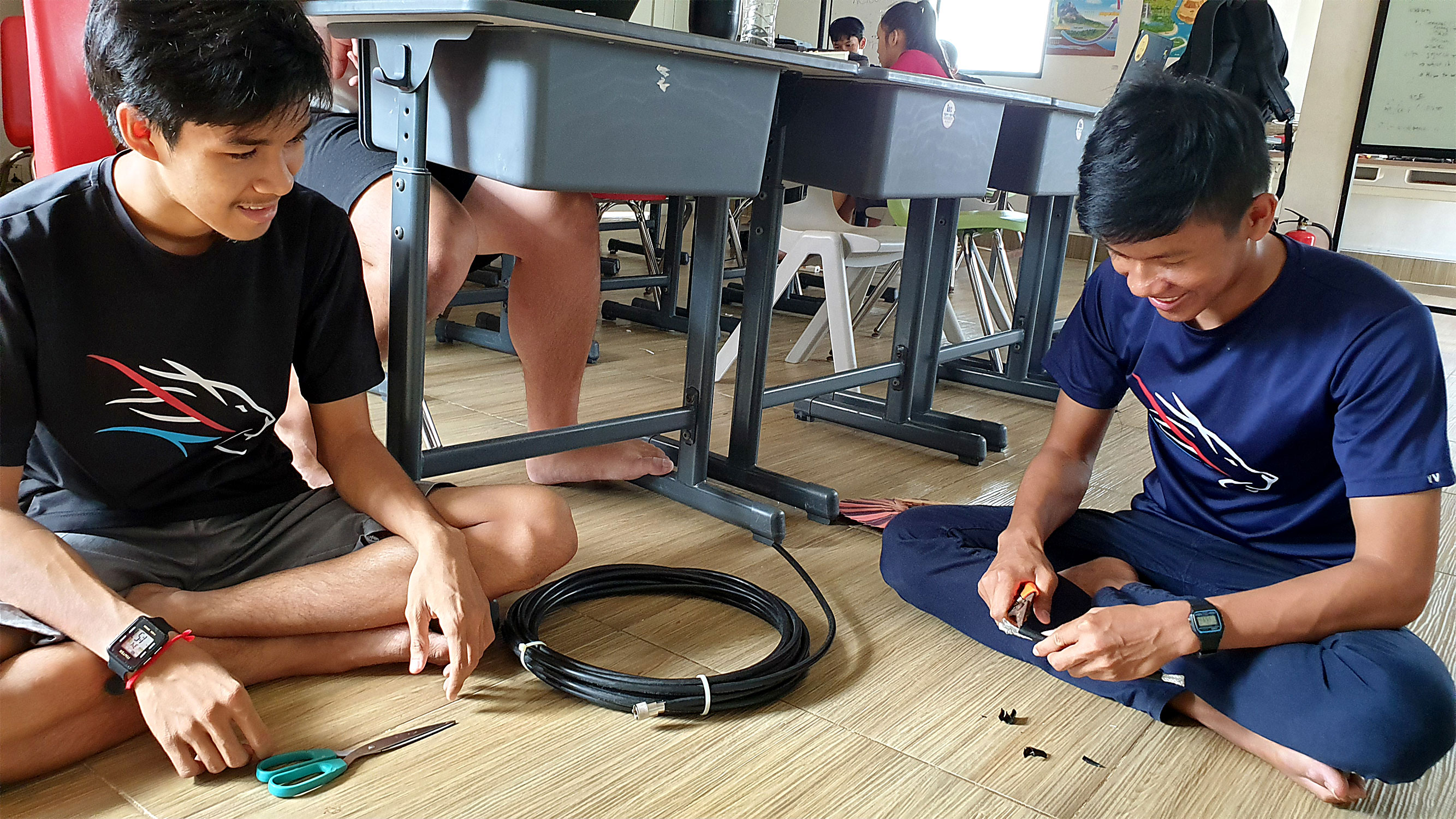 Two Liger Leadership Academy students splice cabling that is part of their Cambodian high school's satellite-tracking ground station.