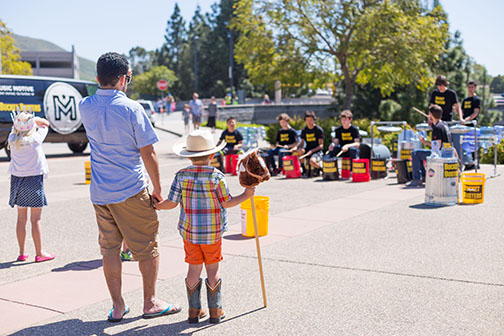 A man and his child watch a group perform at the 2017 Family Day at the PAC.