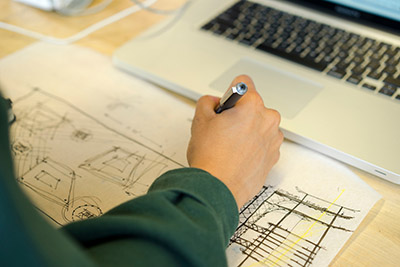 Photo shows a person's arm working on a sketch with a computer also in part of the frame.
