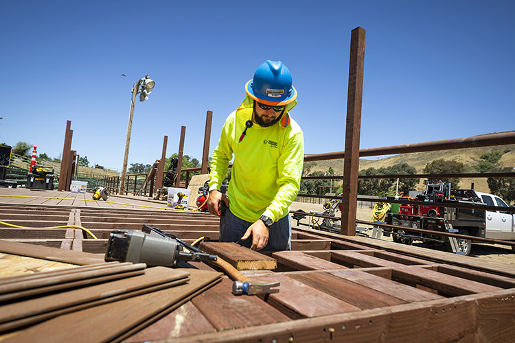 Cal Poly construction management student Ryan Fiorio prepares to use his nail gun to secure deck supports for a rodeo observation deck designed for the university's rodeo arena. The deck will hold a camera that records the practice runs of student riders.
