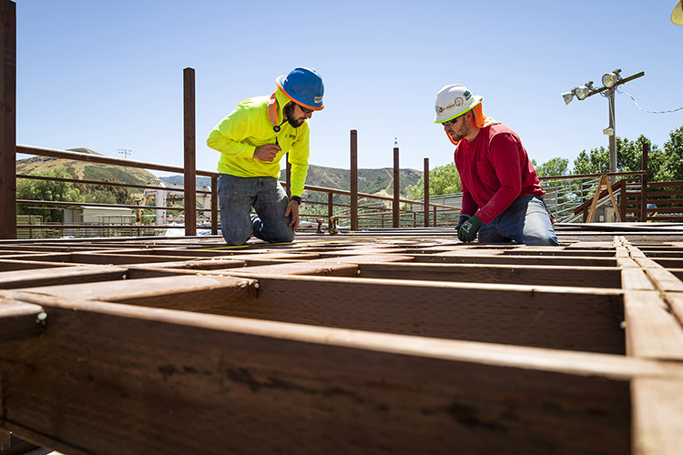 Cal Poly construction management students Ryan Fiorio (left) and Timothy Smith collaborate on building a rodeo observation deck in the rodeo arena designed to record the practice runs of student riders.