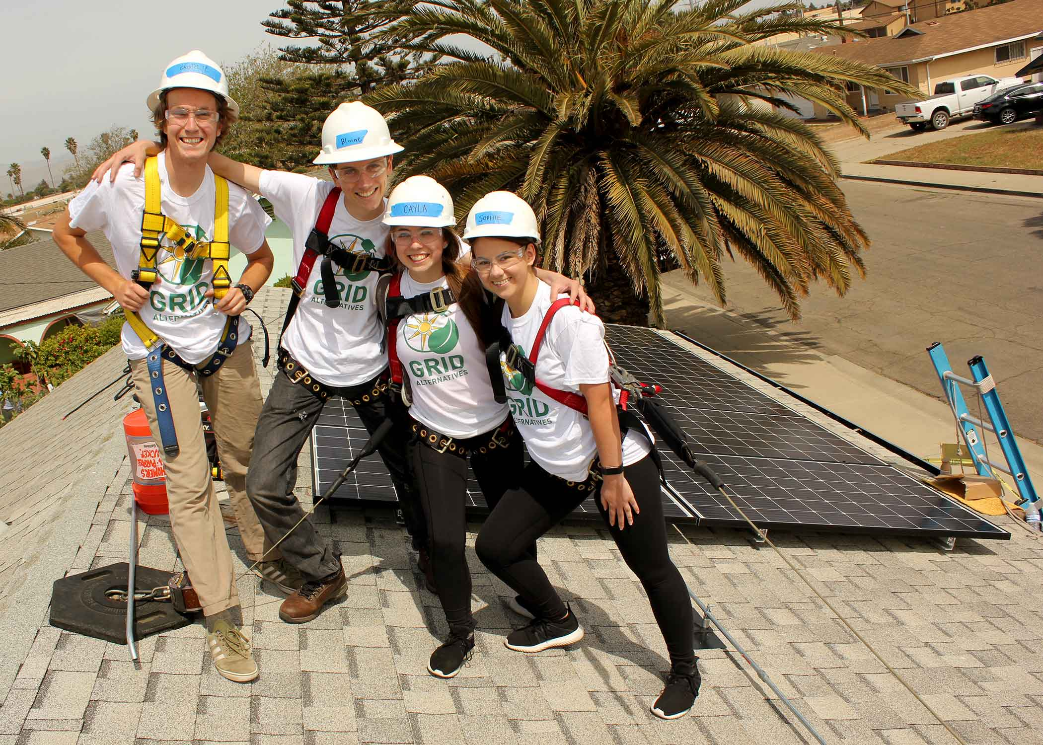 First-year Honors Program students, from left, Charlie Gibbons, a sophomore from Fountain Valley, Calif, who is majoring in environmental management and protections; Blaine Benham, a junior studying biology from San Diego; and mechanical engineering juniors Cayla Quinn of Walnut Creek, Calif., and Sophie Spencer of Phoenix work on a solar panel installation in Santa Maria. A team of six honors students (including those pictured) partnered with GRID Alternatives to create a solar energy jobs guidebook in support of their yearlong service project. Photo by Matthew Aoun, a project coordinator