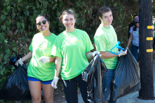 Photo of three students holding trash bags during a previous clean-up day.