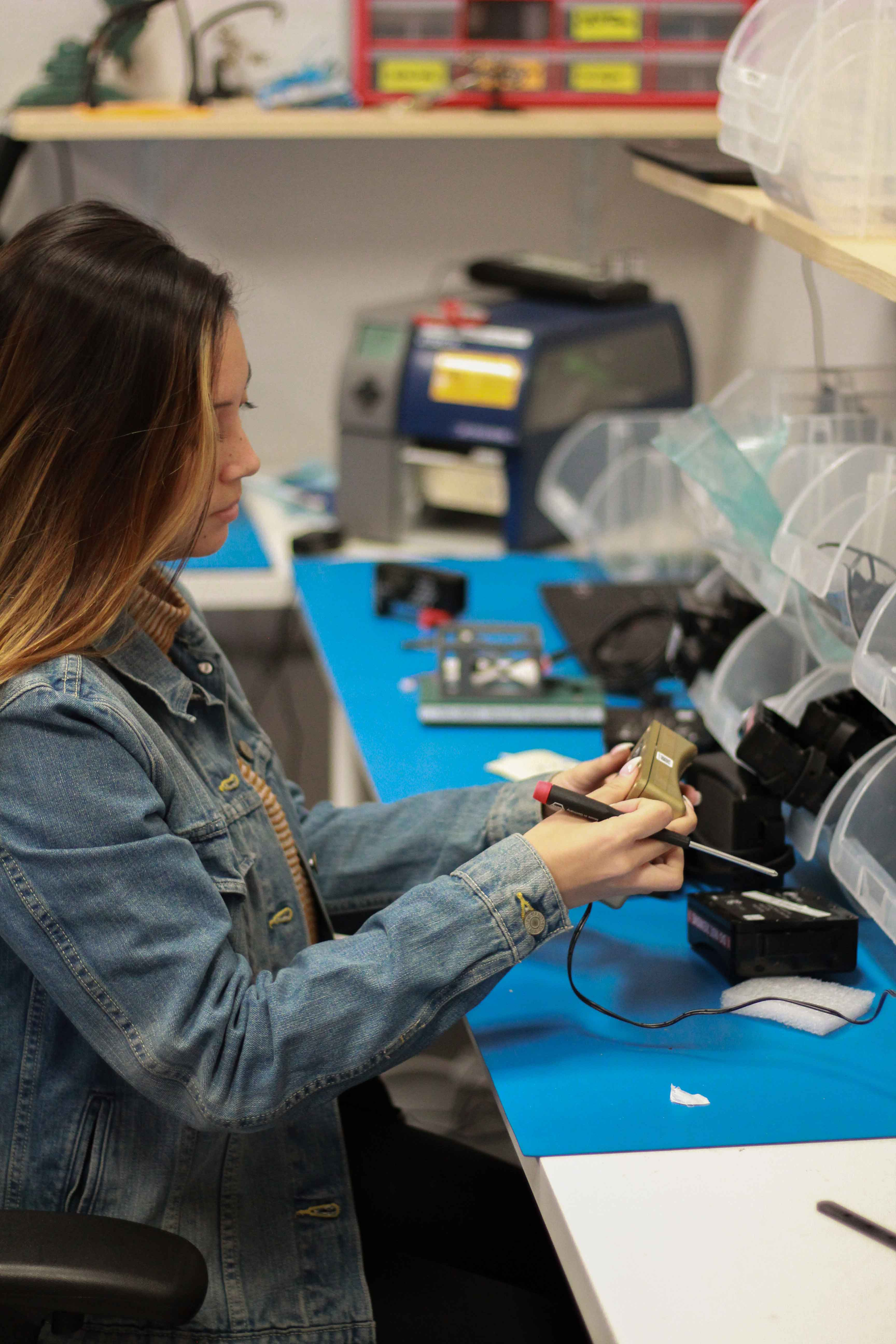 Joanna Birns, a Cal Poly student and customer success representative at startup Flume Inc., works on one of the startup's products in the HotHouse Annex.