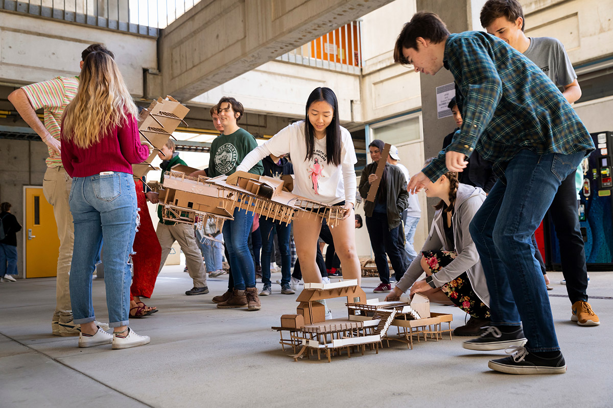 Students carry their cardboard models of the Harford Pier out of their studio classrooms and line them up in the Architecture and Environmental Design Building. From left are students Megan West (in green), Emilie Phuong, Aaron Lowe and Eden Hitzke.
