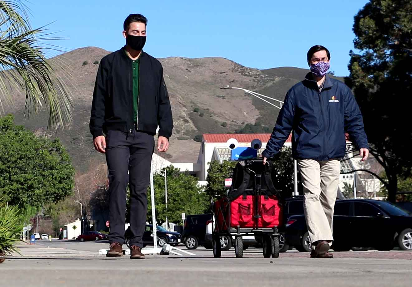 John Seng, right, walks with former student Daniel Jones, now an engineer for Aruba, a Hewlett Packard Enterprise Co. in Roseville, California, with Herbie, a robot Seng created. Seng will use a parallel computing lab, upgraded by HPE, to enhance Herbie's skills.