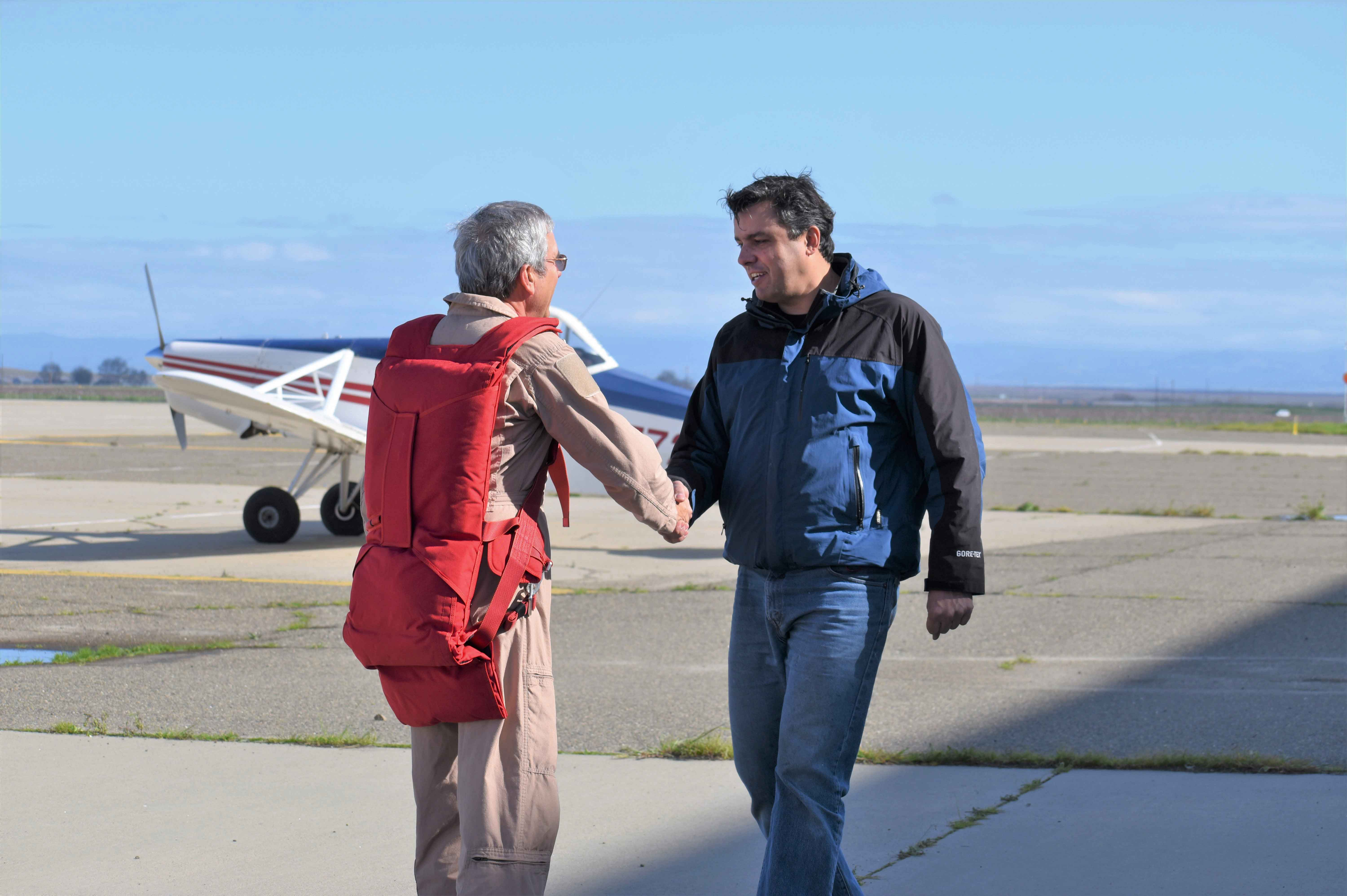 Record-breaking pilot Jim Payne shakes hands with Aerospace Engineering Professor Paulo Iscold at the Castle Air Force Base in Merced. Payne flew a glider created by Iscold and his students.