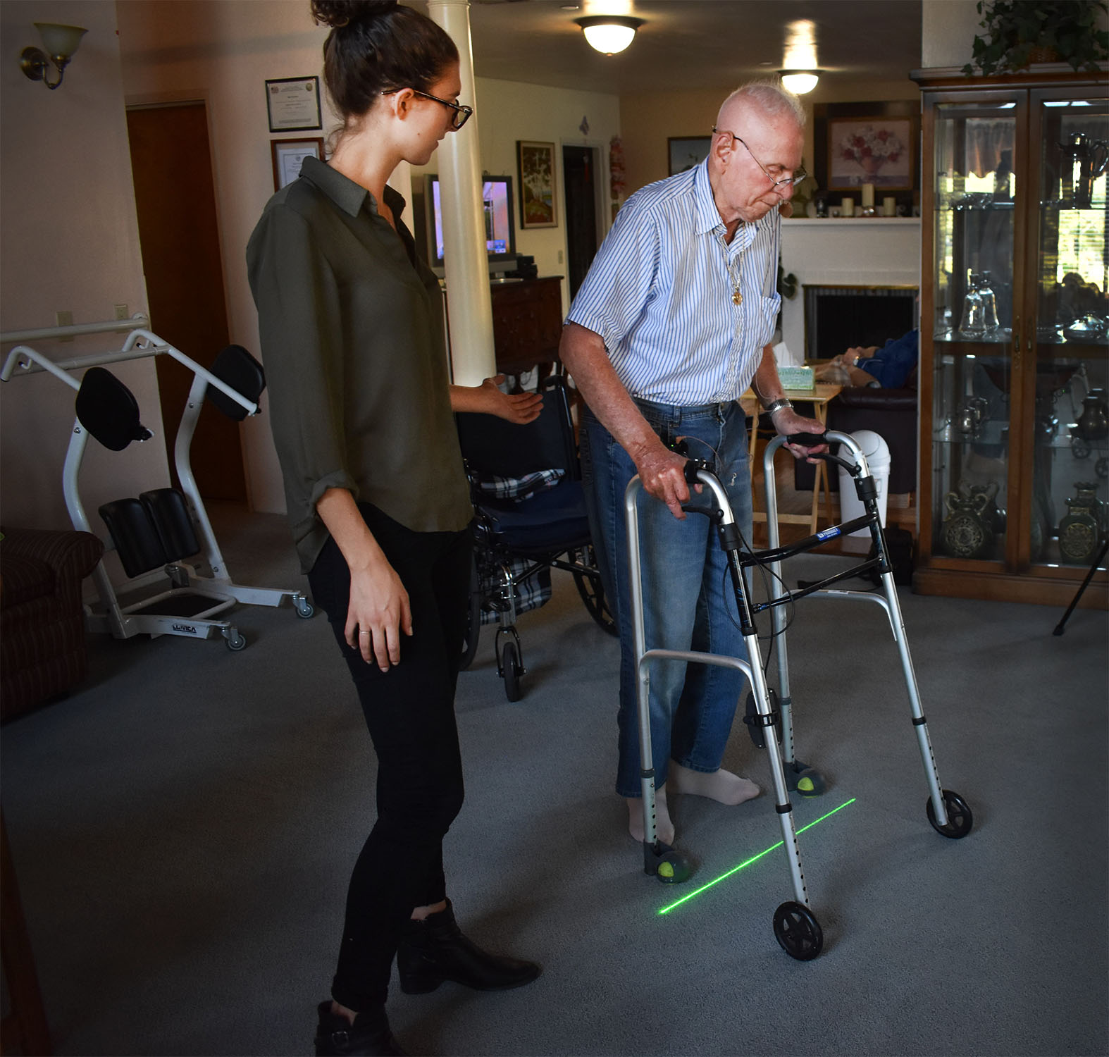"Jack rill demonstrates how he uses the Gaitway, a device created by Collin to help patients with Parkinson's disease walk uninterrupted. The Gaitway is a battery-powered portable that attaches to walkers and canes and use visual and audio cues to interrupt the ""freezing of gait"" symptom that occurs in Parkinson's disease patients."