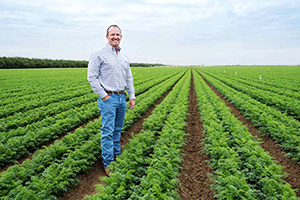 Jeff Huckaby standing out in a field of calf-high row crops
