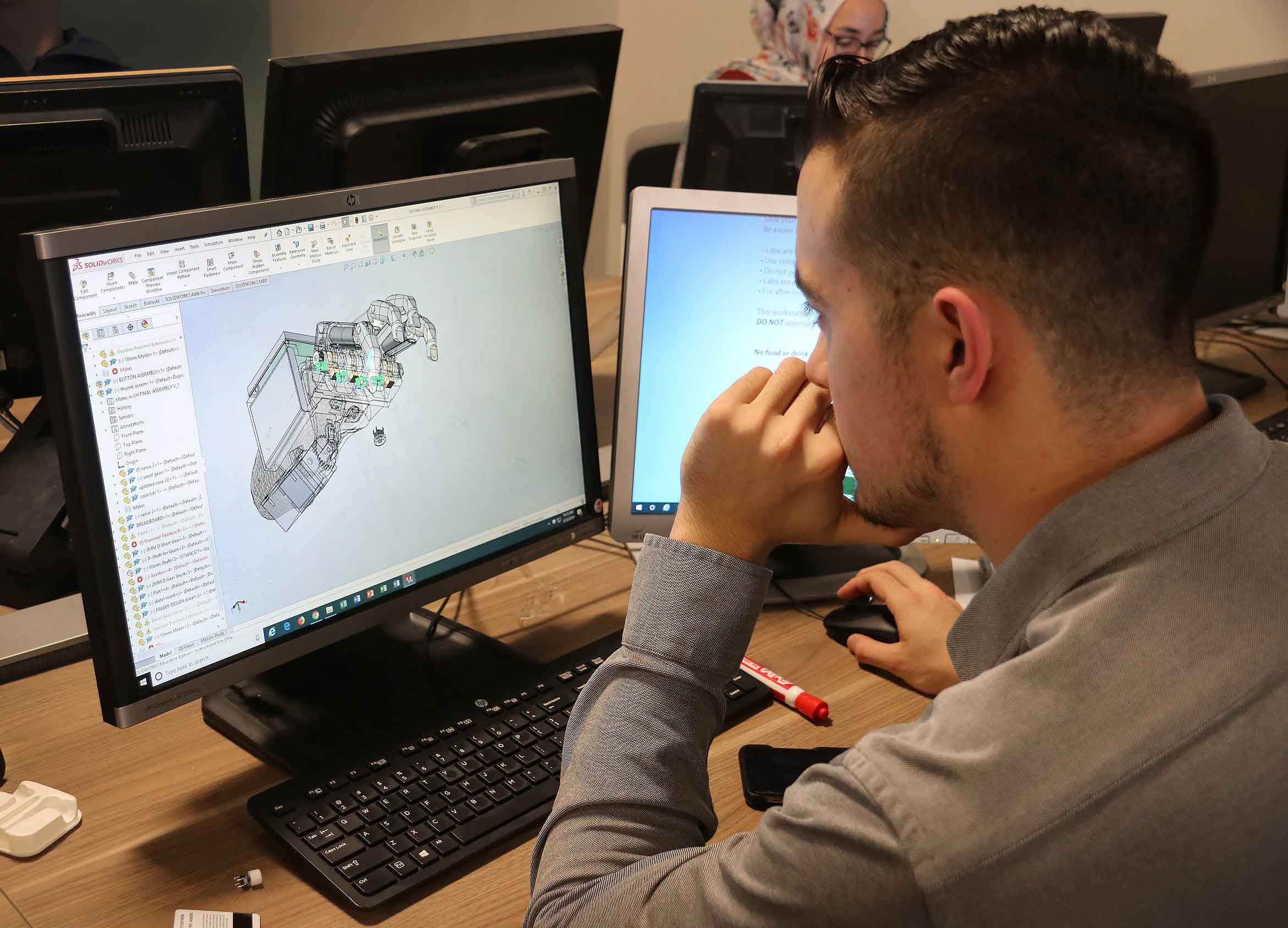 Ryan Kissinger, a mechanical engineering student, shows a computer-aided design of Julian's robotic hand.