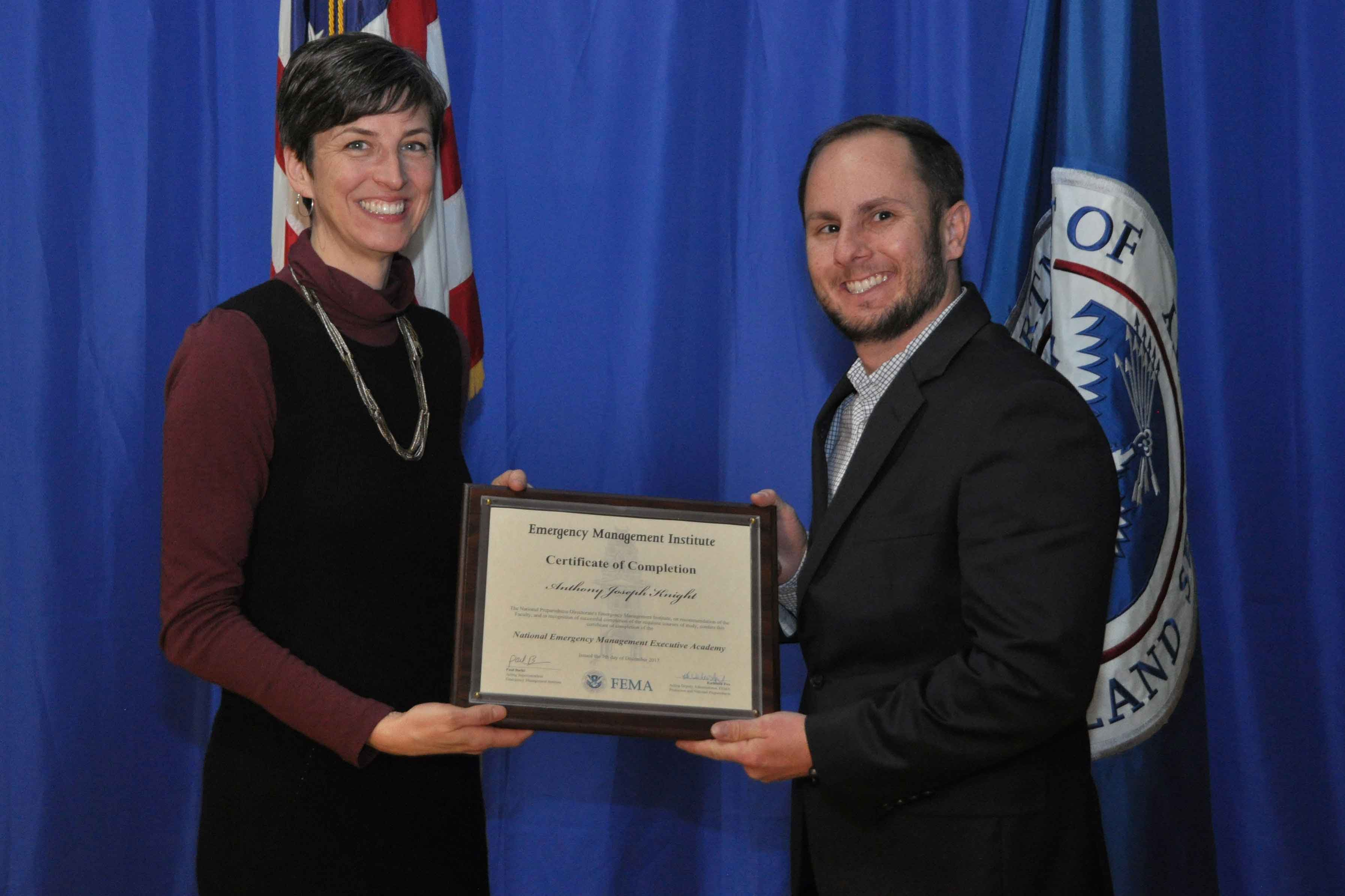 Anthony J. Knight, Cal Poly's director of emergency management, graduated Dec. 7 from FEMA's National Emergency Management Executive Academy. Katie Fox (left), FEMA acting deputy administrator, protection and national preparedness, congratulates Knight.