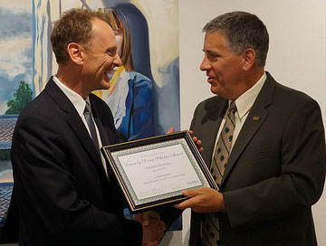 Kinesiology professor Kevin Taylor receiving the Learn by Doing Scholar Award from President Armstrong in 2015.