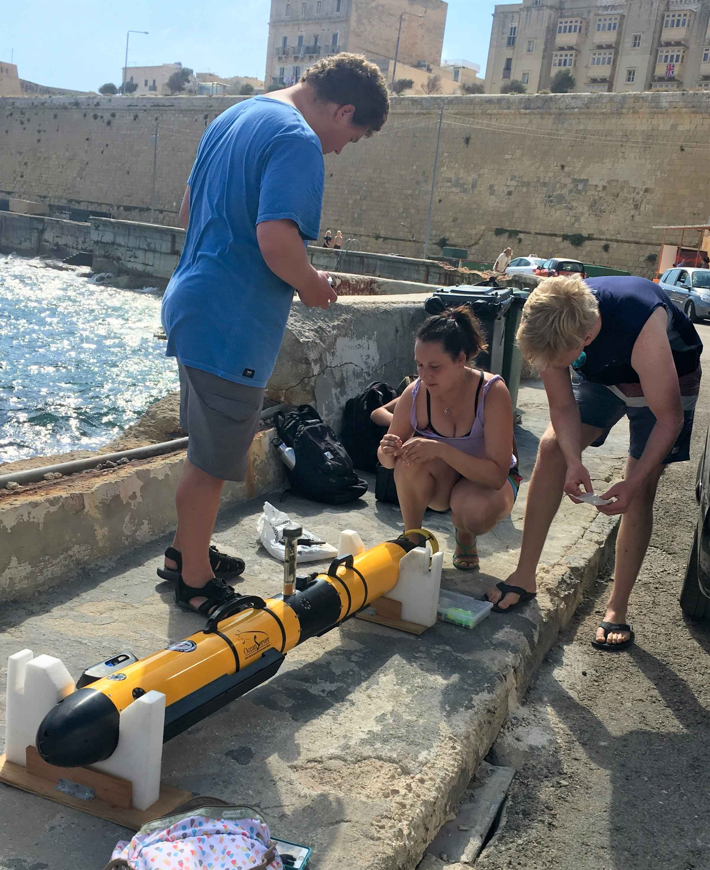 Cal Poly students Bonita Galvan from San Antonio, Texas (center) and Kolton Yager (left) prepare an automated underwater vehicle with a student from Harvey Mudd College during a day of exploration off the coast of Malta.