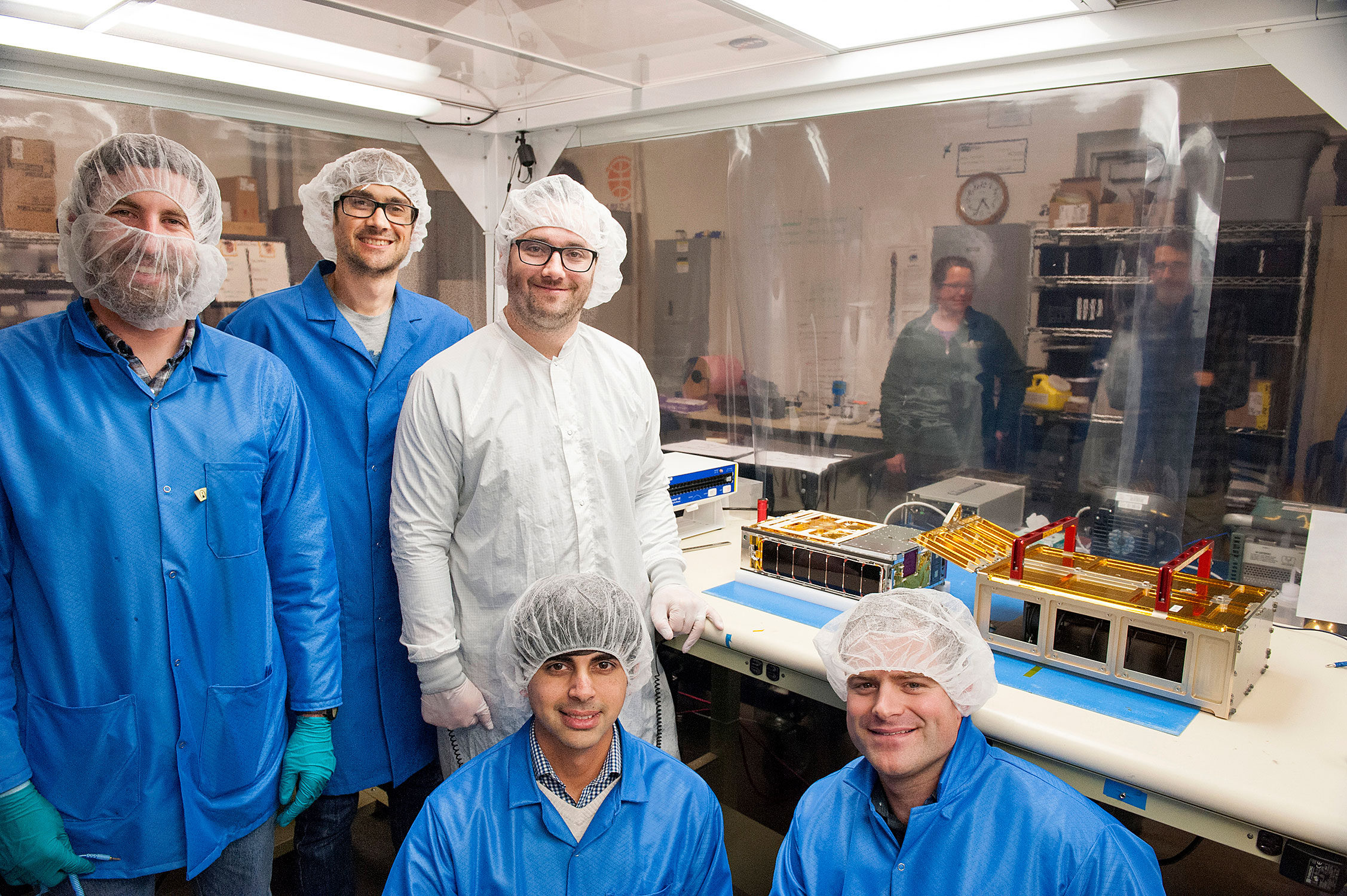A team of engineers assisted in integrating the MarCO CubeSats into their deployment boxes on March 2-3, 2018. Standing from left, Justin Carnahan, a Tyvak mission manager and Cal Poly alumnus, and the Jet Propulsion Laboratory's Danny Forgett, a thermal systems engineer, and Joel Steinkraus, MarCO lead mechanical engineer; kneeling are (left) Vidur Kaushish, another mission manager at Tyvak Nanosatellite Systems, and Cal Poly aeronautical engineer Dave Pignatelli.