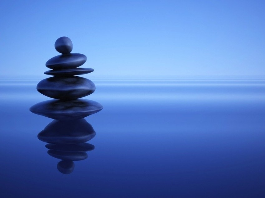 Photo of smooth stones stacked on a beach.