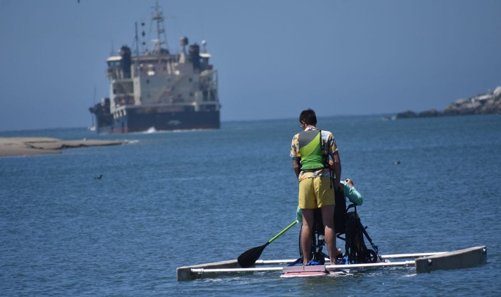 Cal Poly engineering student Alexander Holthaus demonstrates his team's adaptive paddleboard to Randy Coffman of Central California Adaptive Sports Center as the Army Corps of Engineers' 200-foot Yaquina dredges the harbor in Morro Bay, California, in this photo from the summer of 2019. Dredging can impact tides, sometimes leading to flooding, according to research from Cal Poly Professor Stefan Talke
