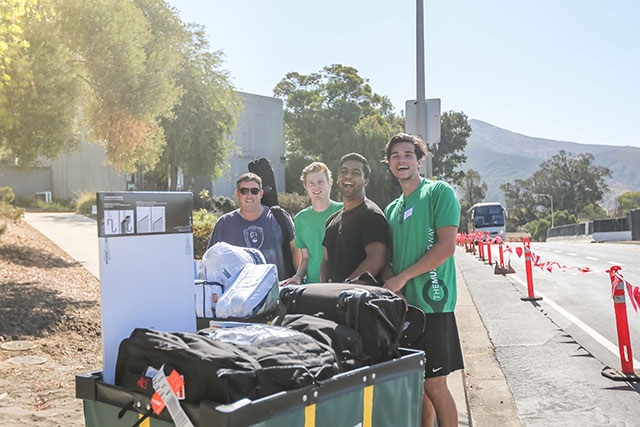 Photo of student and volunteers during Move in weekend.