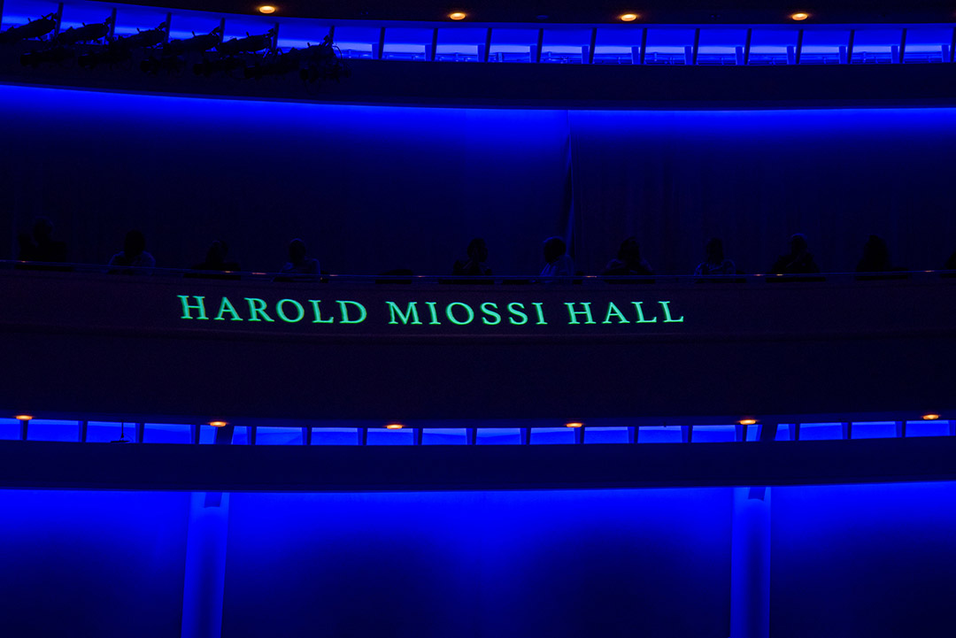 Photo of inside of the PAC, low blue lighting with the name Harold Miossi Hall. Photo credit Heather Nguyen Photography.