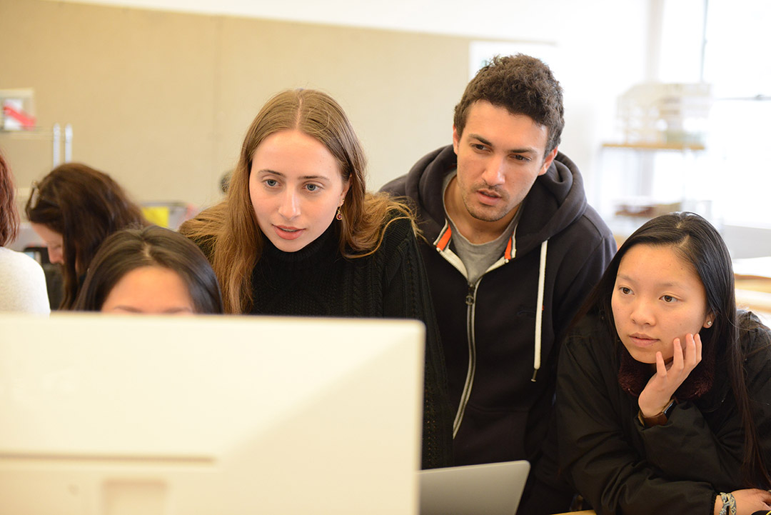 From left to right, Nicole Lo, Katherine Young, Nathan Chudnovsky and Sirina Law peer at a computer while working in a recent design studio class taught by architecture faculty member Stacey White.