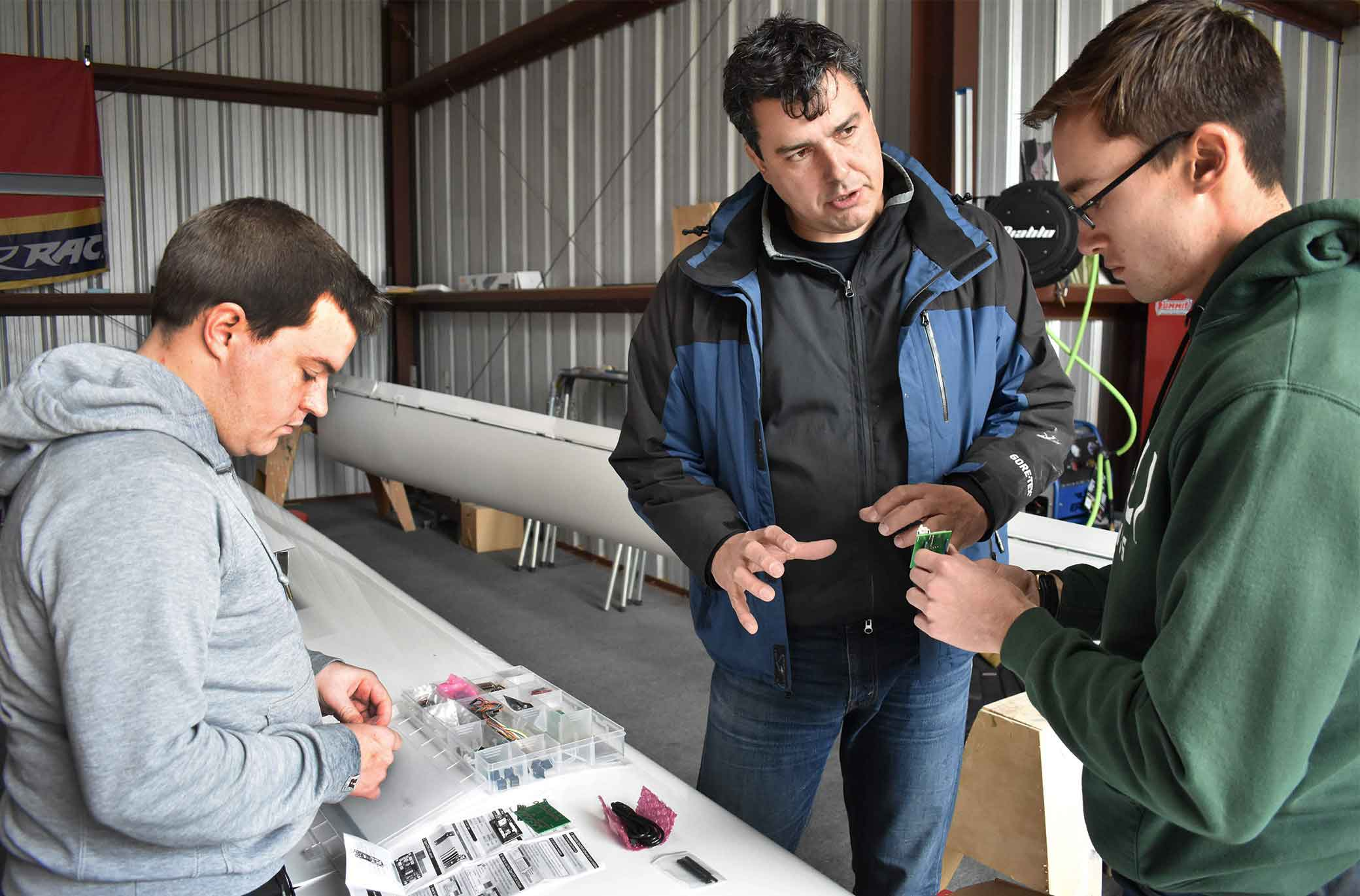 Aerospace engineering students Patrick Chizek, left, and Luke Bughman, right, work with Professor Paulo Iscold on his sail plane, which features a 93-foot wingspan.