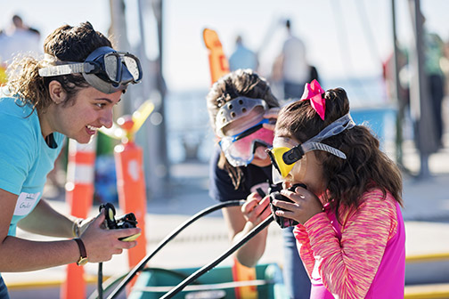 A Cal Poly student shows a young girl how to breath through a scuba regulator.
