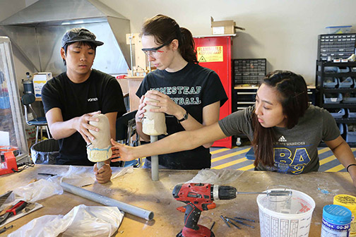 Mechanical Engineering students Paul Song and Nina Yadlowsky, and Materials Engineering student Belle Liwag work on a soft socket for a prosthesis in the QL+ Lab.